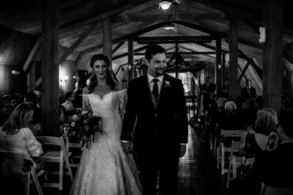 bride-and-groom-down-aisle-ceremony-at-rustic-manor-1848.jpg