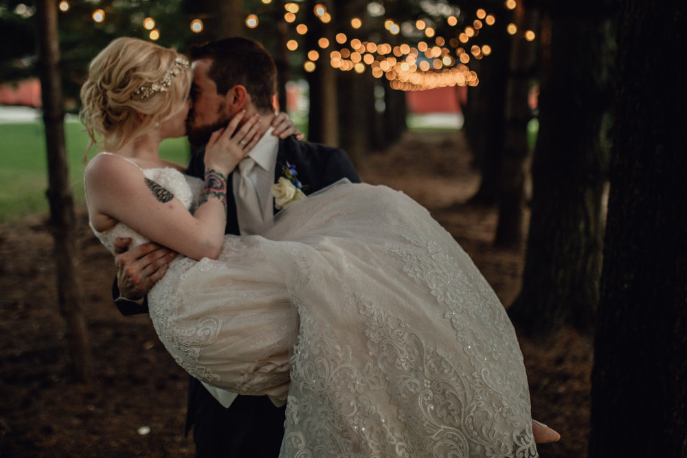 groom carries bride kiss under string lights in forest at oak hill weddings path of pines