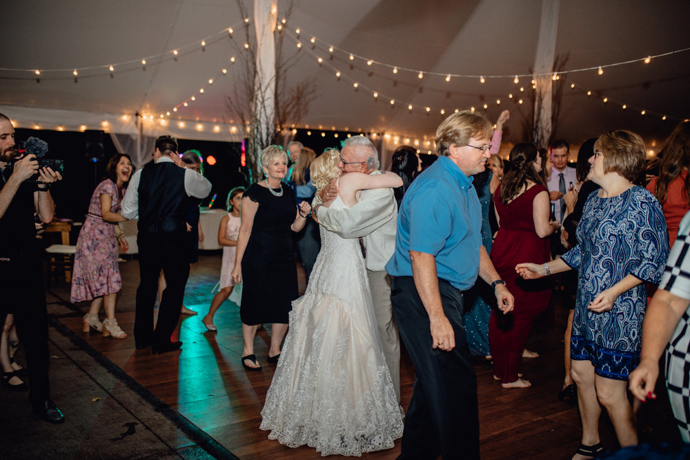 bride and groom and guests dancing under tent at oak hill weddings