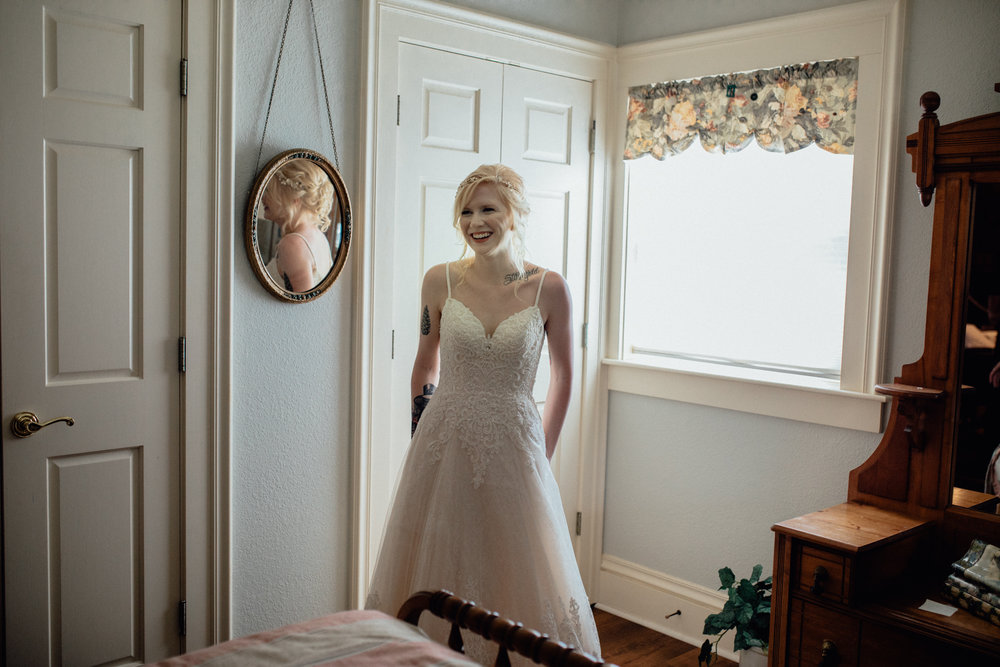 Bride posing in dress by mirror