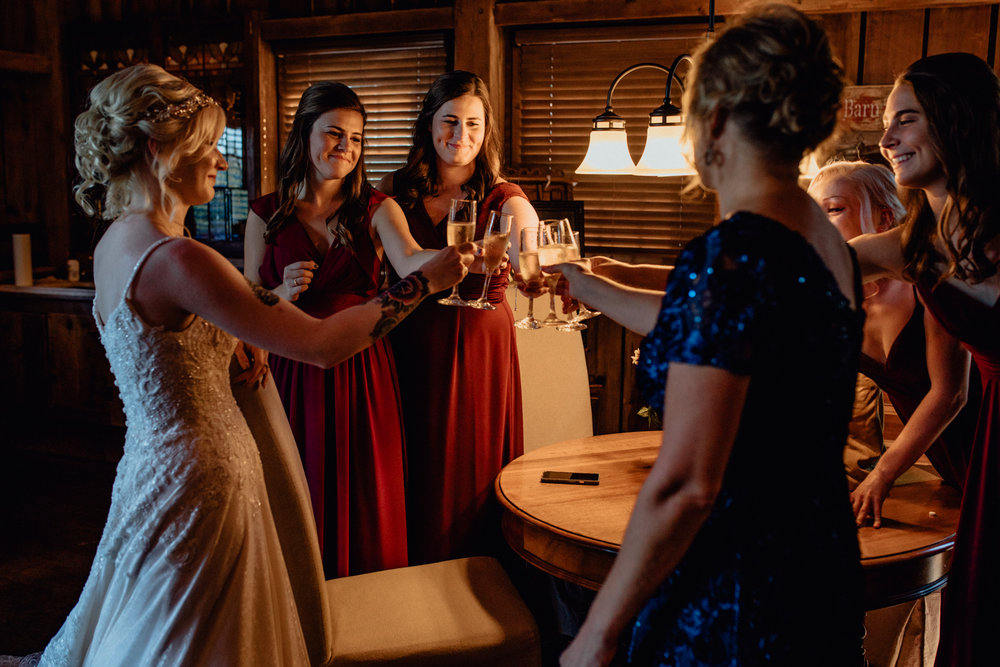 Bride and bridesmaids cheers champagne before ceremony in barn at oak hill weddings