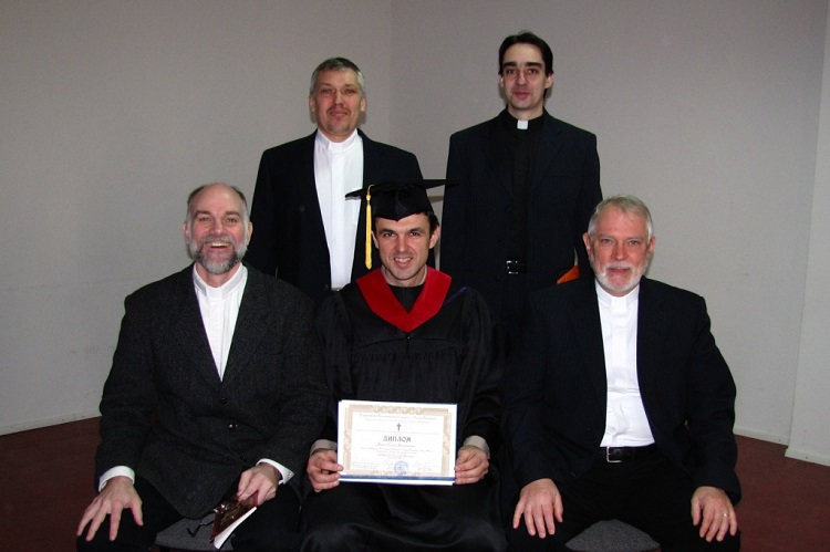 Seminary graduate with professors and staff.