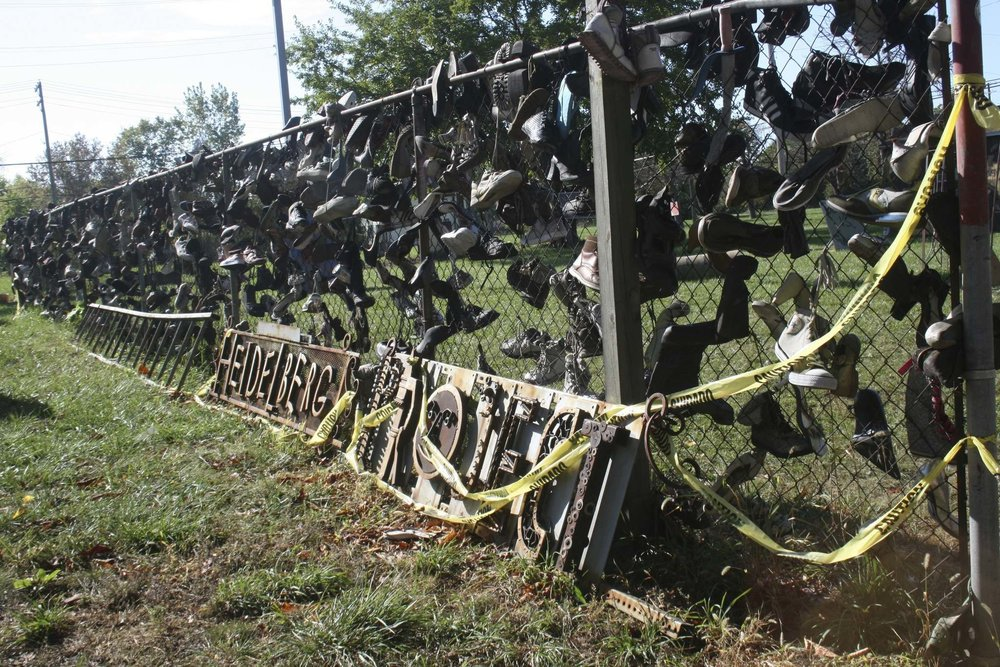 A fence on Heidelberg Street is covered in old, worn shoes.  Photo by Leesa Dahl