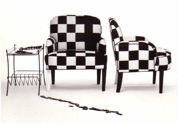 Domino checks fall off this appliquéd chair with a single white painted leg.