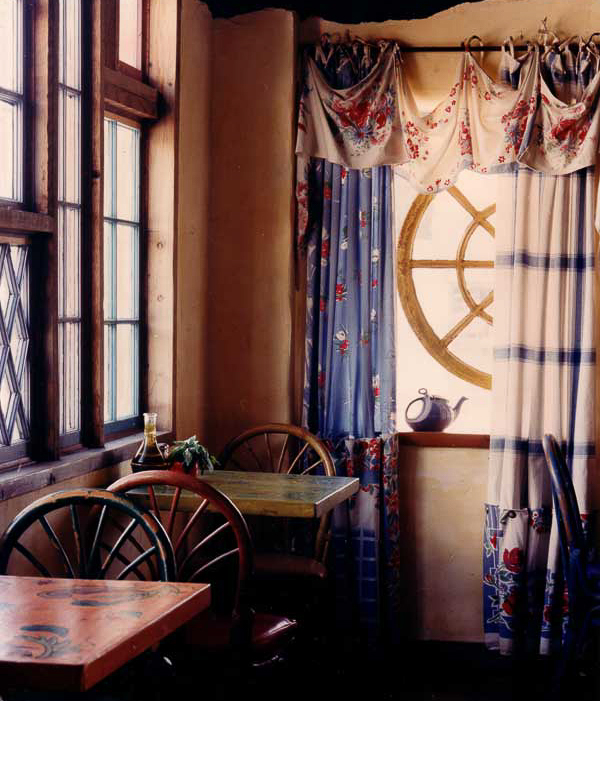 Old found windows mounted on the side face of the building allow for better visibility from the street. 1950's tablecloths with vintage buttons were used on the windows.