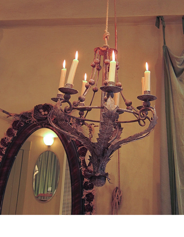Large candle chandeliers and long wool and silk trimmed curtains, offer an elegance to the shop.