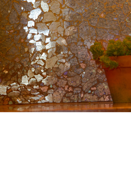 Back splash material is made of fragmented automobile glass by Ellen Blakely. She backs the glass with various reflective papers and cracks are filled with copper grout.