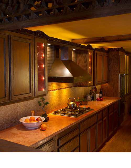 Balinese frames were cut and installed on the top crown of cabinets. Warm gel colors were used over lights behind them.