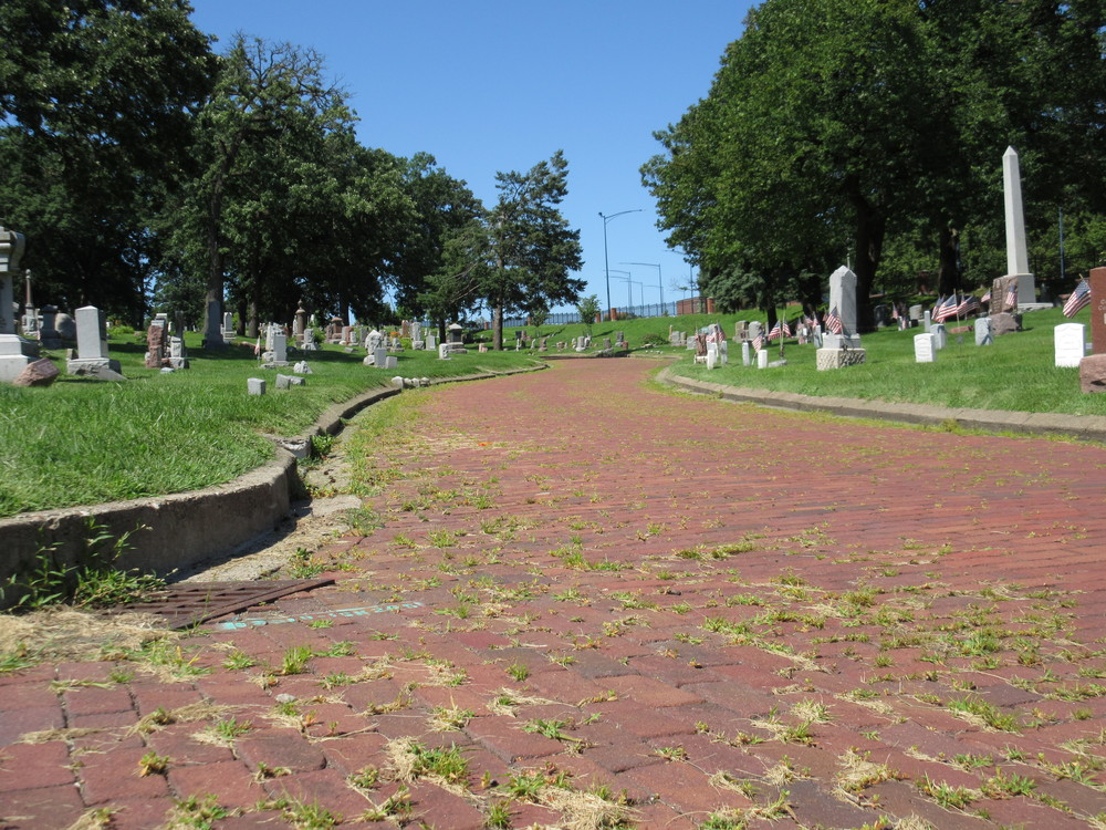 Brick street looking north with a stormwater inlet in Woodland Cemetery.