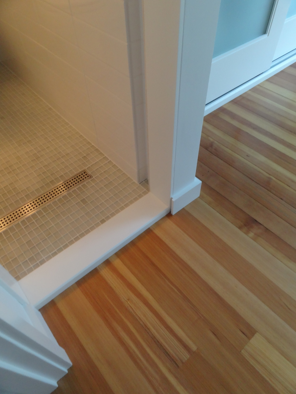 Materials - glass tile, ss trench drain, heart pine flooring, Corian threhold