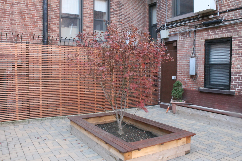 Completed - new wood screens, planters, paving and trees