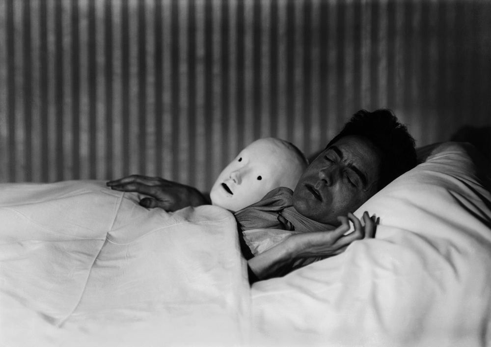 Berenice Abbott (1898 - 1991) COCTEAU IN BED WITH MASK, PARIS  1927 Gelatin silver print; printed later 10 1/2 x 13 1/2 inches 26.7 x 34.3 centimeters Courtesy Howard Greenberg Gallery, New York CR# AB.36266