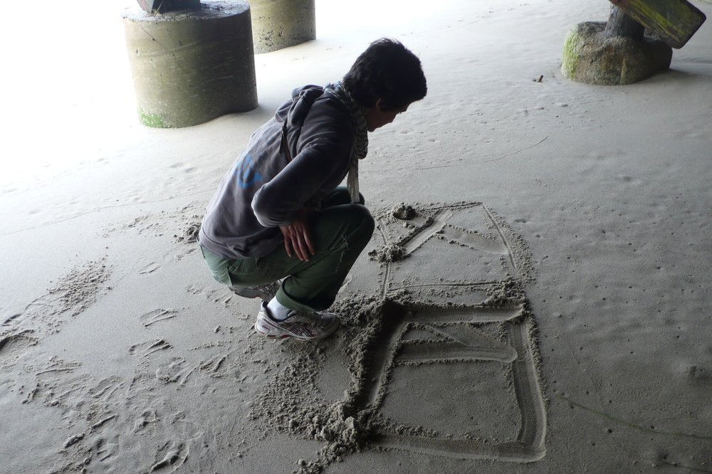 AH drawing in sand under house #2