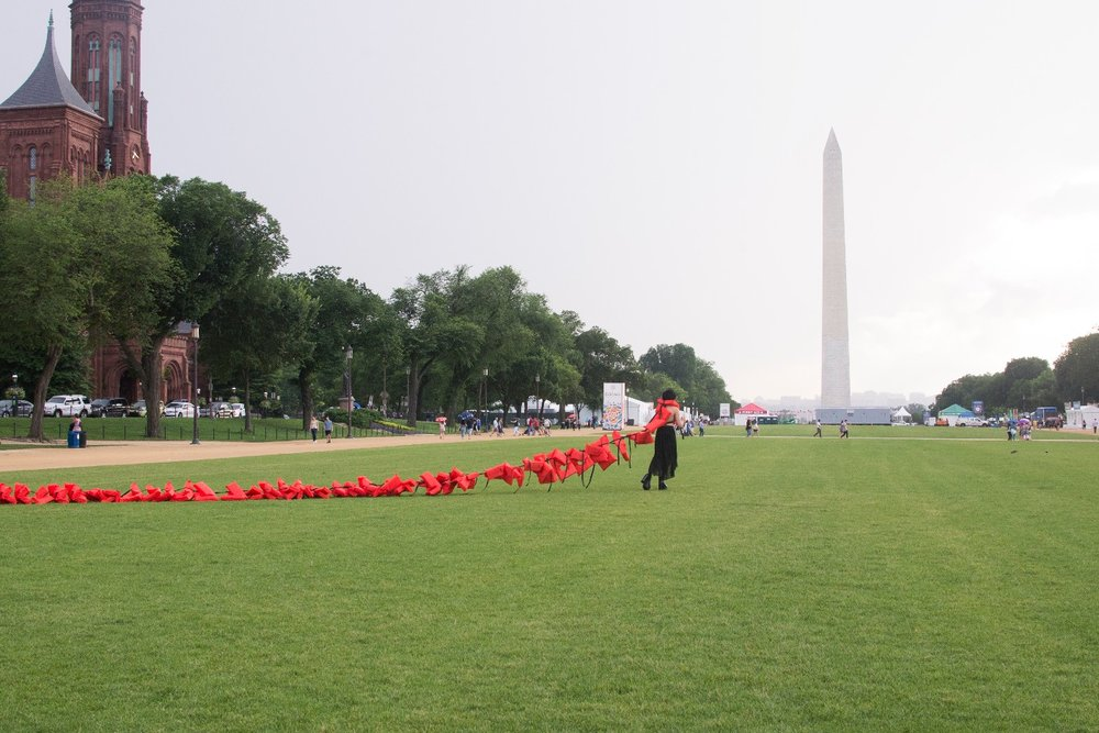 Repatriation  -performance on the National Mall that began inside the Smithsonian Arts & Industry Building for  By the People 2018  hosted by Halcyon Arts Lab, 2018, 86 life vests, Buddhist chime, & audience participation, varied dimensions