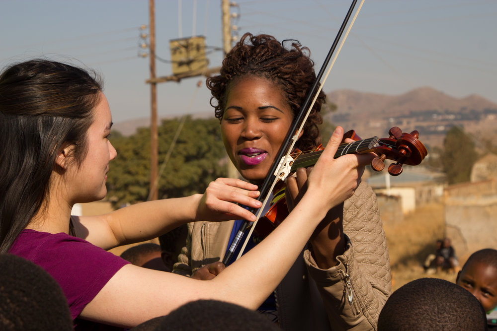 Anna showing Londiwe--a Shepherd at Gege CarePoint and a graduate of Swaziland Leadership Academy--how to play the violin. Because Gege is a very rural part of Swaziland, this was the first time that anyone at the CarePoint had ever seen a violin. (Personal favorite part of the trip for Anna!)