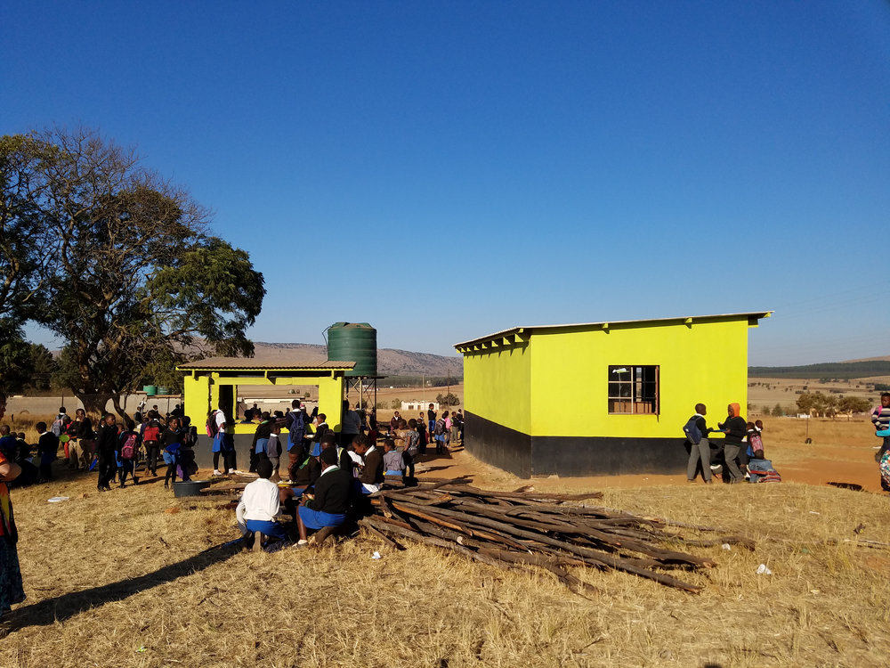 Gege Carepoint, June 2016.   From left to right--cooking structure, water silo, and preschool. The CarePoint also has a multipurpose building and chicken coop that are not pictured.