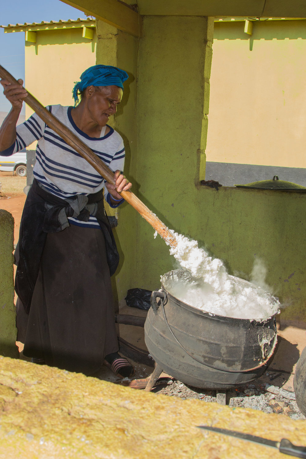 In the Gege CarePoint kitchen, Gogo (Grandmother) Norah stirs maize meal. It takes a lot of strength to stir (Anna can testify to this--she tried and failed).