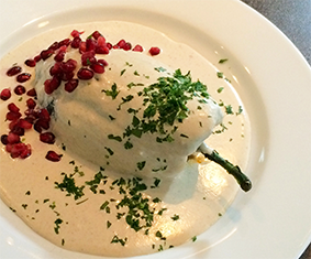 Chile Poblano filled with picadillo (chopped beef and pork meat, nuts, fruits and spices) topped with a Nogada Sauce (walnut-based dairy sauce) garnished with pomegranate seeds and parsley.