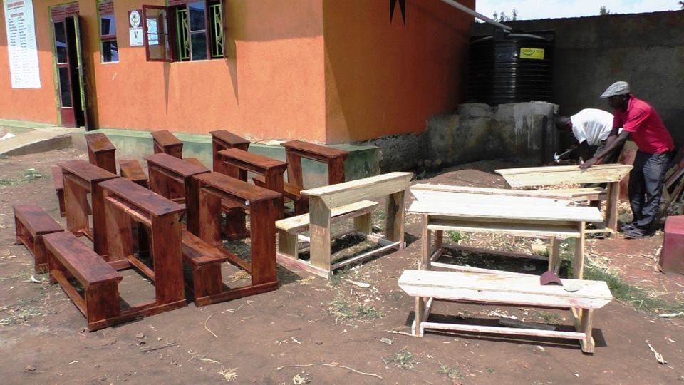Workers construct desks at the Bizoha campus. Each desk can hold three primary school students.