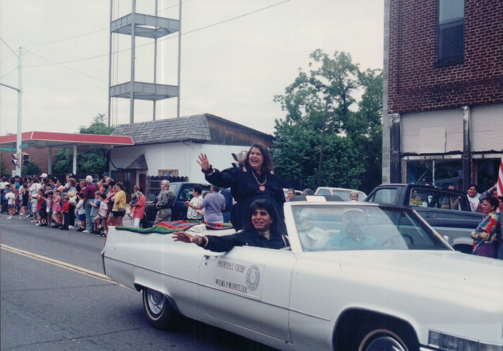 Wilma Mankiller and Charlie Soap wave during a parade while she is Prinicpal Chief