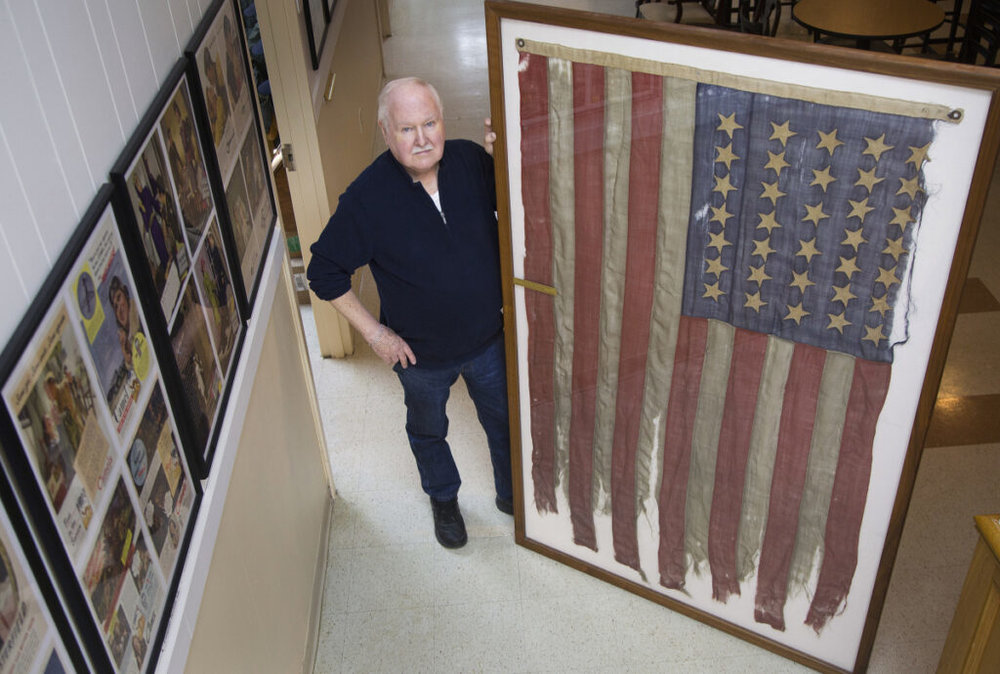 Lee Humiston of the Maine Military Museum receives flag from the Civil War that he says was the first to fly over Texas shores. The flag belonged to Major James H. Whitmore of the Fifteenth Maine Regiment. Staff photo by Derek Davis