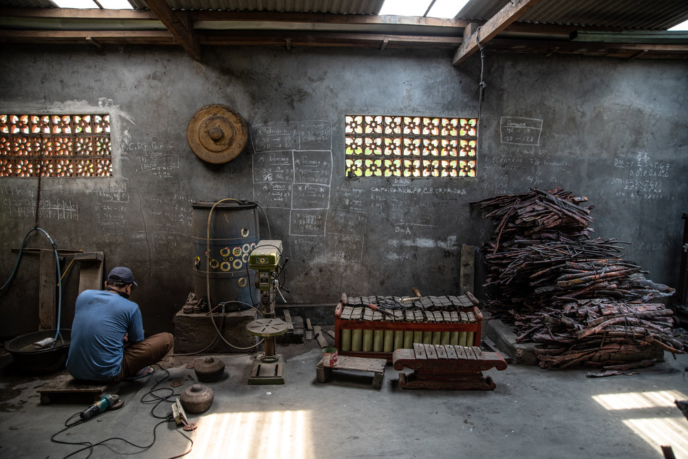 Gamelan maker works machine to polish smaller gongs
