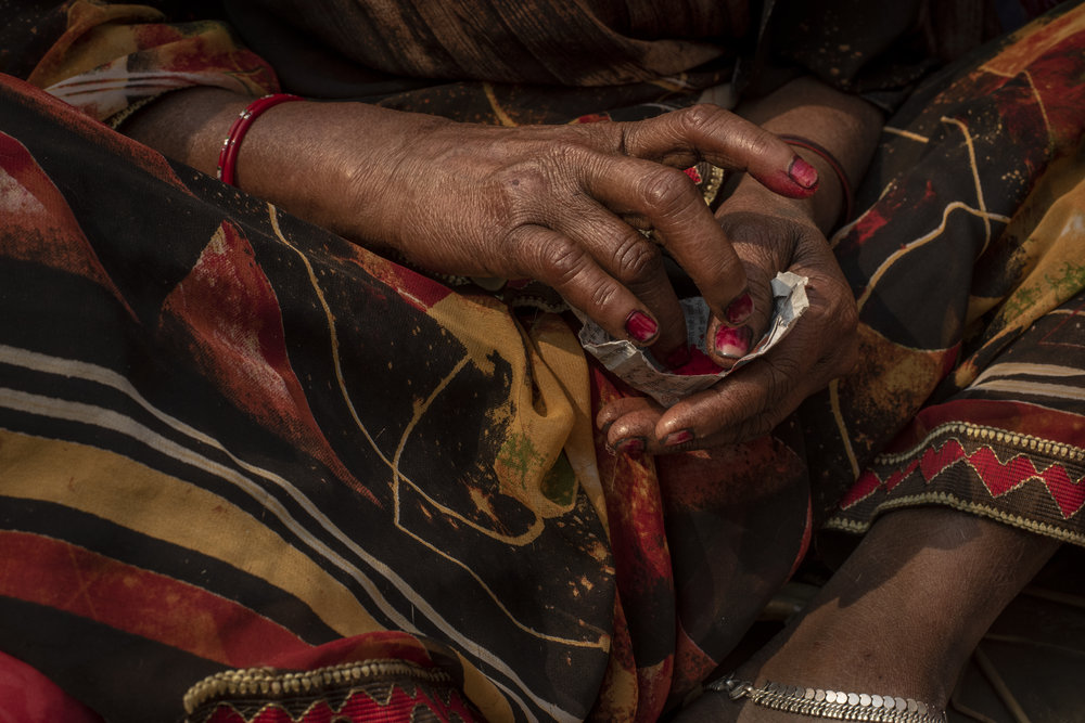 Woman prepares colored pigment to apply a bindi to her forehead