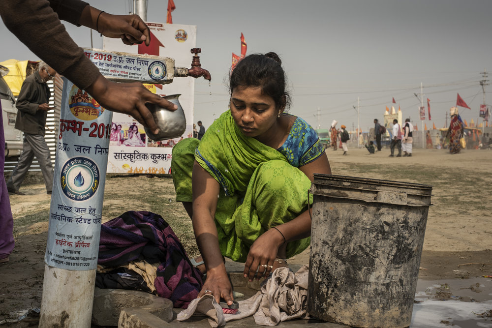 Woman cleans clothes at the roadside faucet.