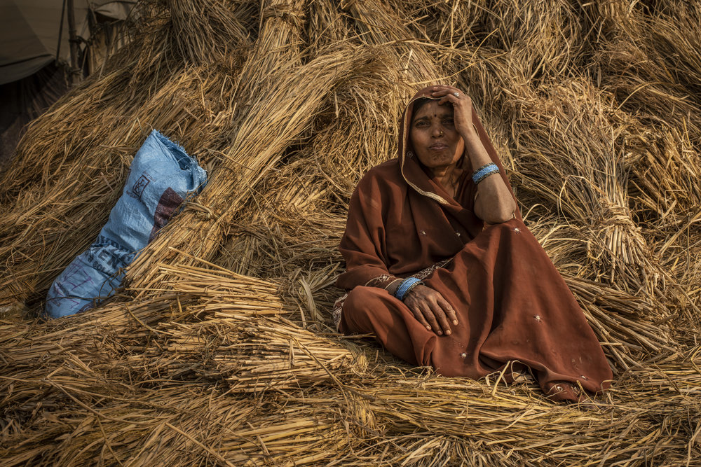 Woman rests on a bale of hay.