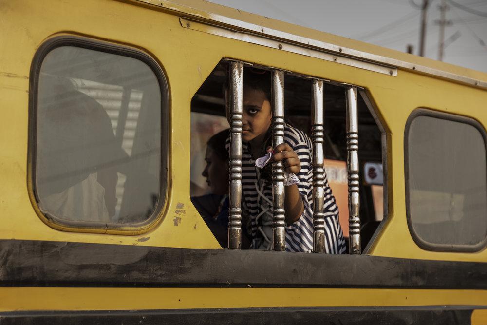 Girl gazes through the bars of a passing Tuk Tuk