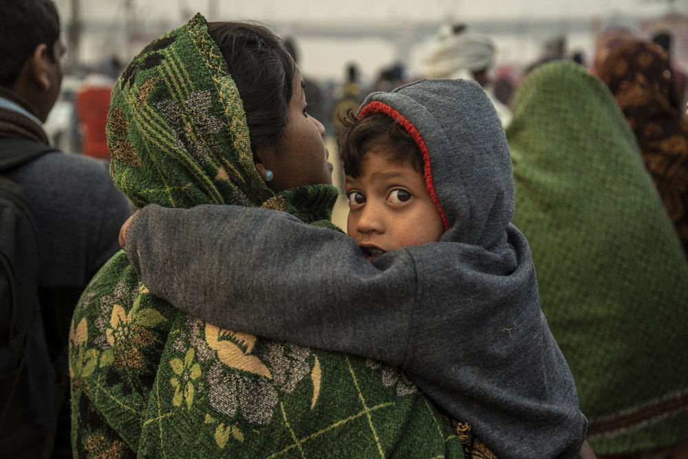 Mother and child march towards the center of the mela