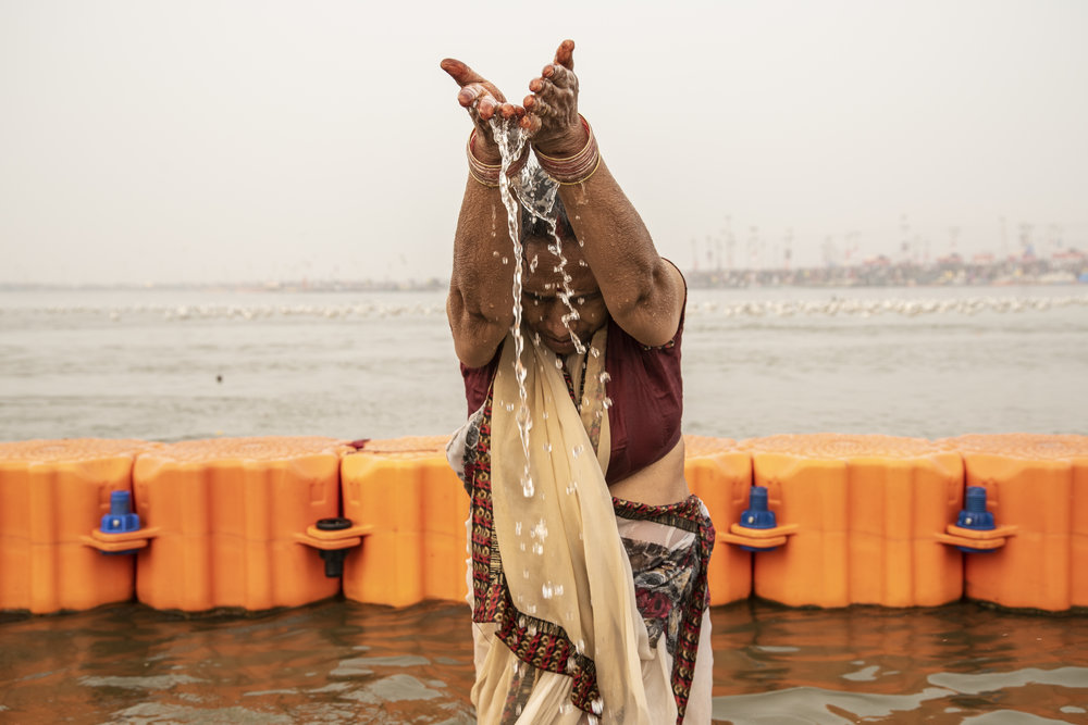 Woman pours the holy water of the Ganges from her hands