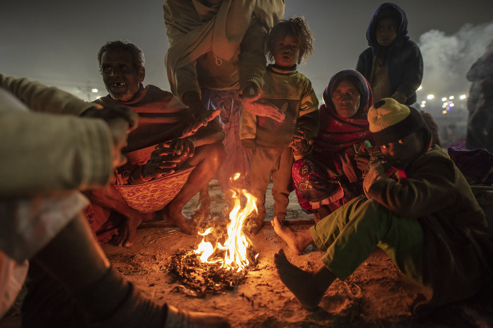 Huddled by a fire, a family gathers on the outskirts of the Mela, preparing for their morning walk to Ganga.