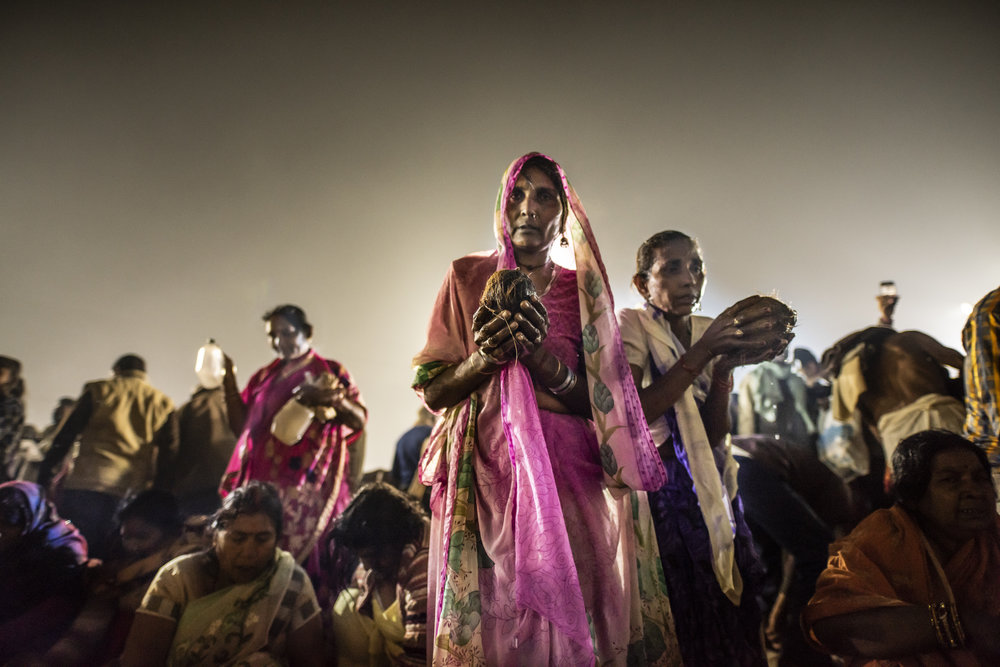 Women push through the crowd to bring puja offerings to the Ganges.
