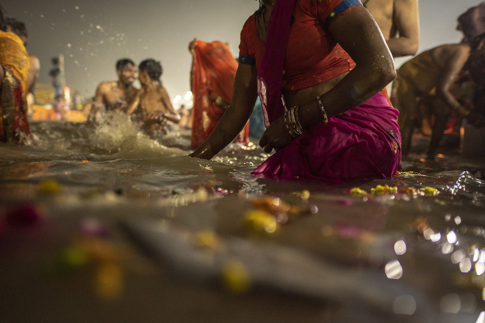 Petals float in the Ganges as men and women gather to bathe