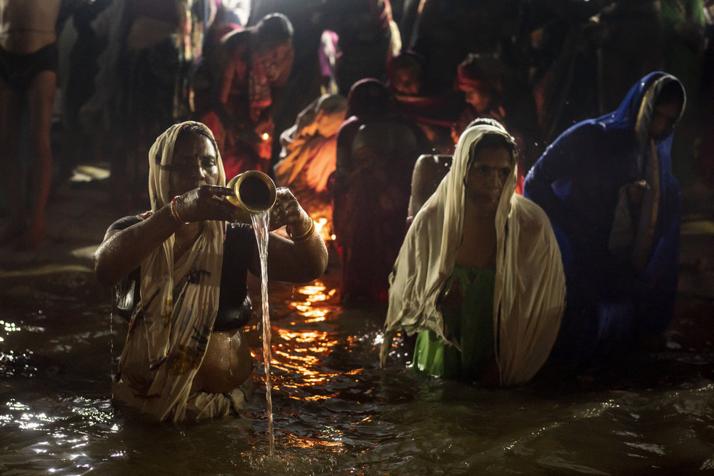 Women gather at the shores of the ganges, pouring water from lota pots, lighting puja offerings and performing ablutions