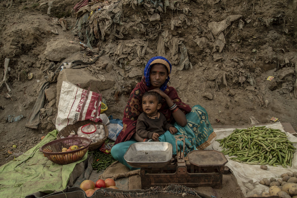 A mother sits with her toddler and sells produce roadside.