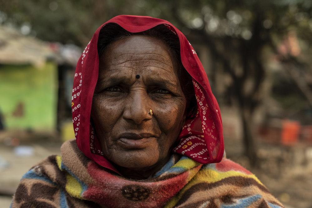 """Chanda Devi, age 70, lives in a small swampy copse just outside of Sangam with her children and grandchildren. After spending a few minutes with her it was apparent that she was the matriarch of this family, shooing away curious bystanders and keeping the children in check. After sharing some chai I asked if I could do a portrait of her. She shook her head saying """"I am poor and most of my teeth are missing"""". I smiled and asked my partnerto tell her that I do not see her poverty, all I see is beauty. Her eyes lightened and she nodded. May beauty always transcend circumstance."""