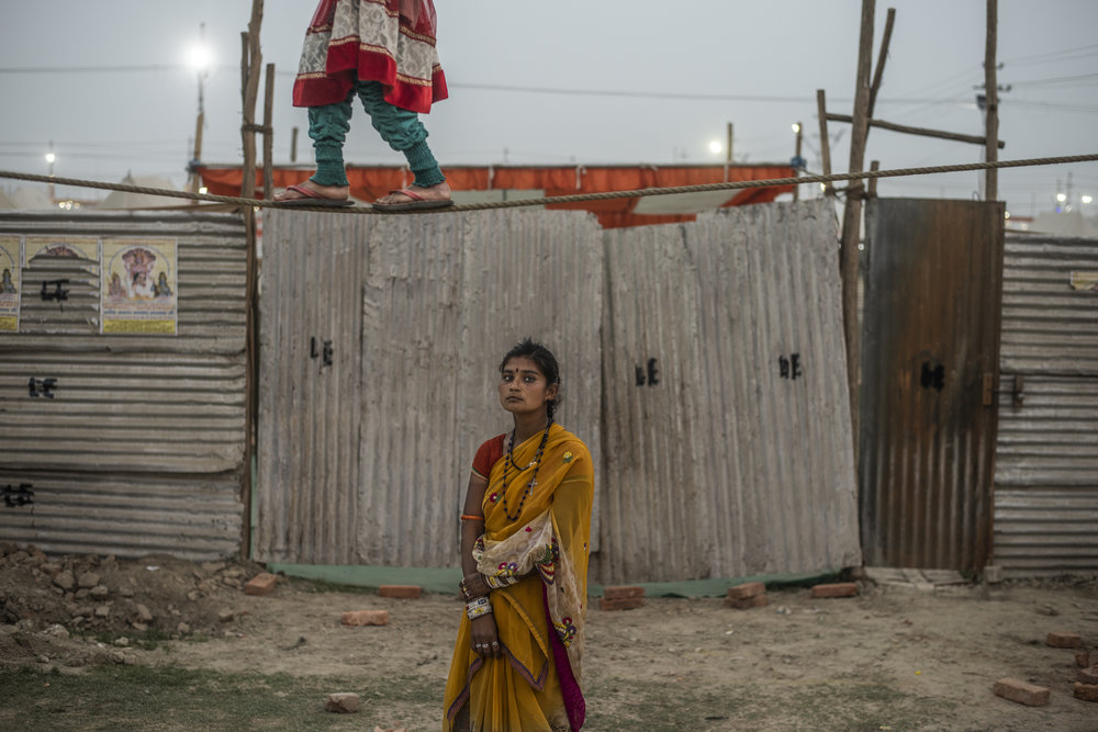 A young girl balances on a tight rope while another stands stoically below to collect money from bystanders. One of the many carnival-like acts that occurred in the often whimsical landscape of the Kumbh Mela. There's something about this girls austerity that struck me. With so much theater, her face seemed to reveal something true. Something hidden behind the colorful facade.