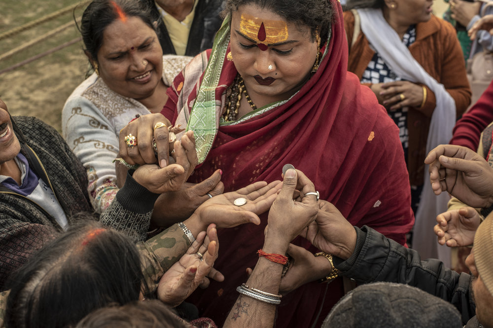Mayuri Ma blesses coins and receives money offerings from followers.