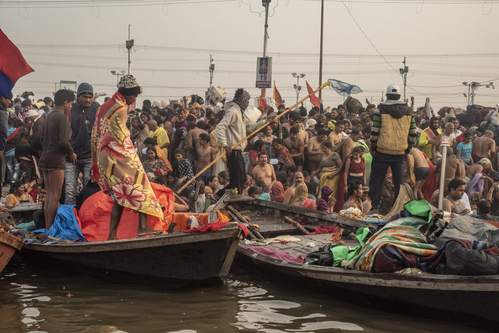 Boats line the shore as a mass of people gather to bathe in the ganges