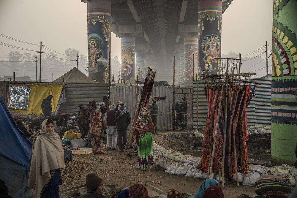 People gather beneath a painted cement bridge within the Mela.