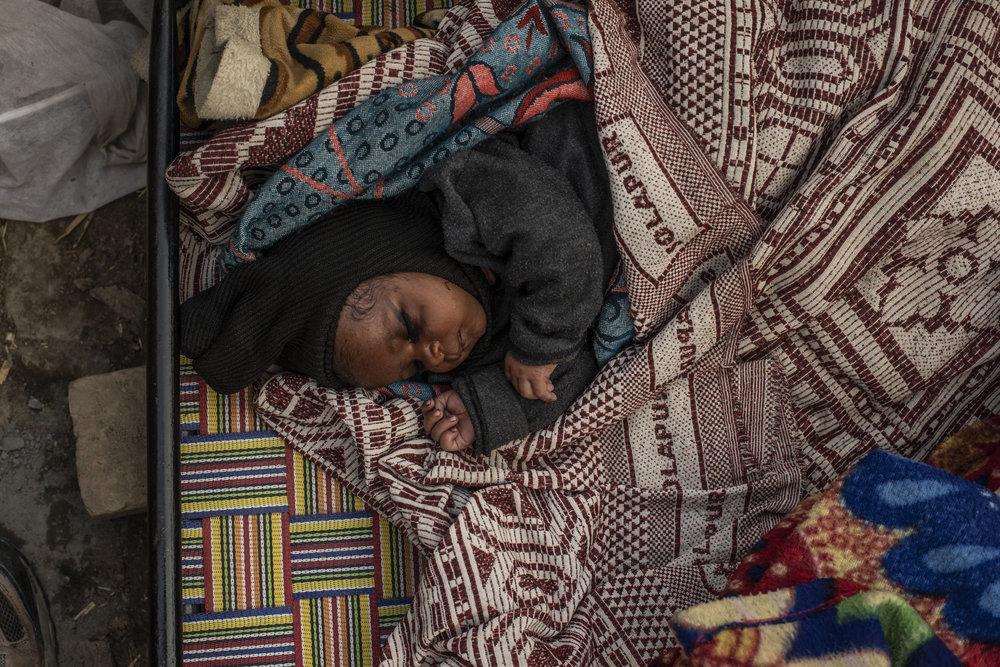 One month old granddaughter of Vimla sleeps on cot.