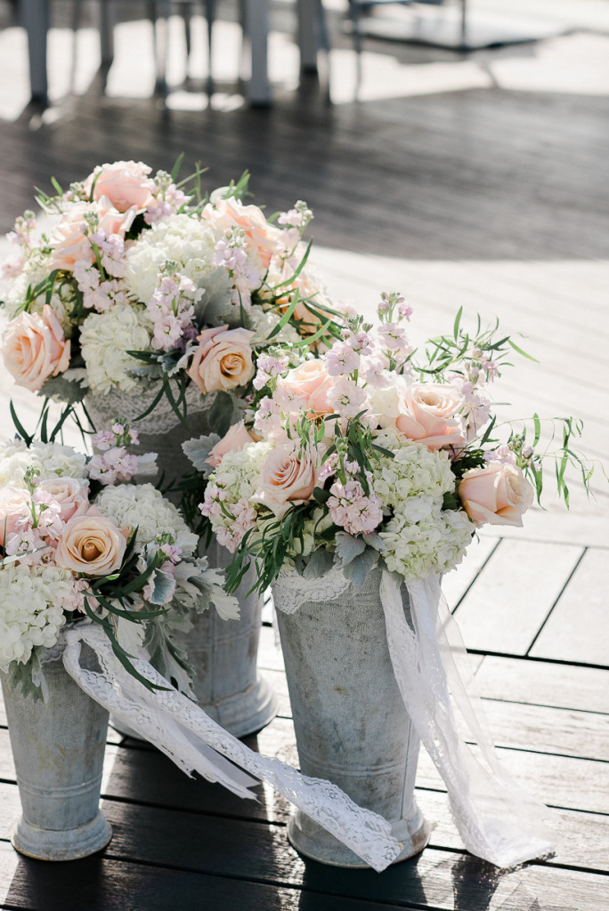 A trio of  galvanized buckets  were filled to the brim with hydrangea, roses, stock, and greenery.  We accented them with pieces of lace to help go with the flowy, beach theme.