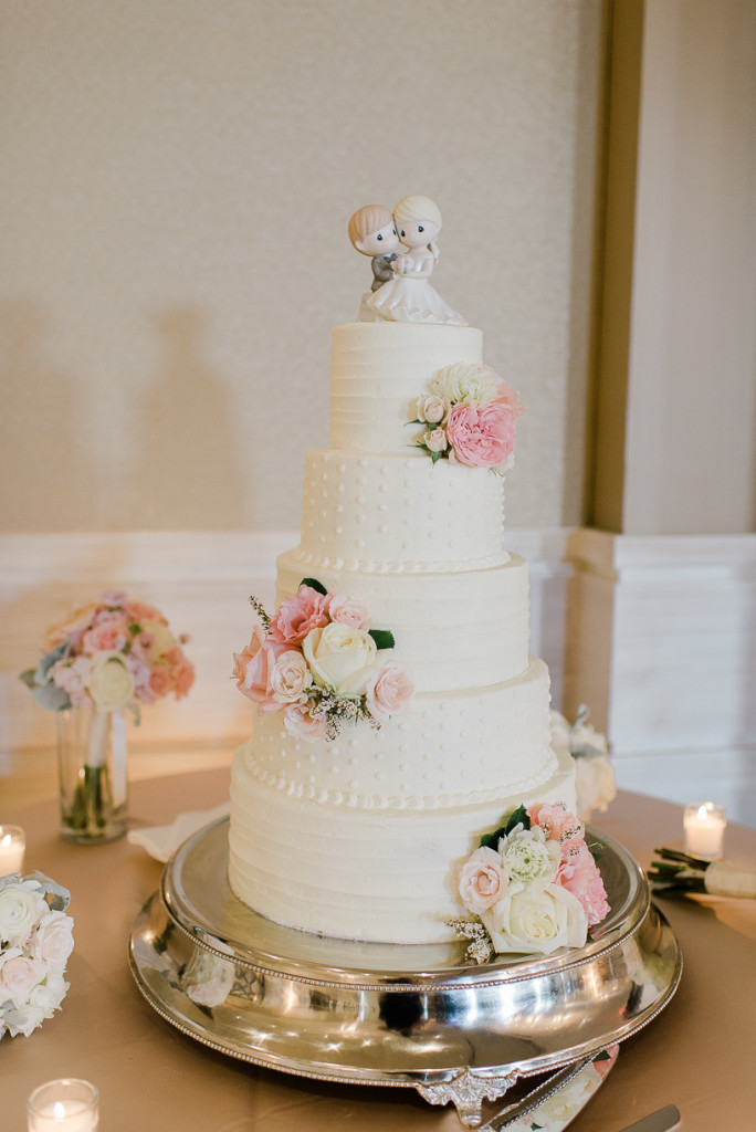 How cute are these cake toppers! We love using flowers to do some cake decoratingand really finish the look of the room. Garden roses,spray roses, waxflower, ranunculus and lisianthus brought just enough color to this beautiful white wedding cake.