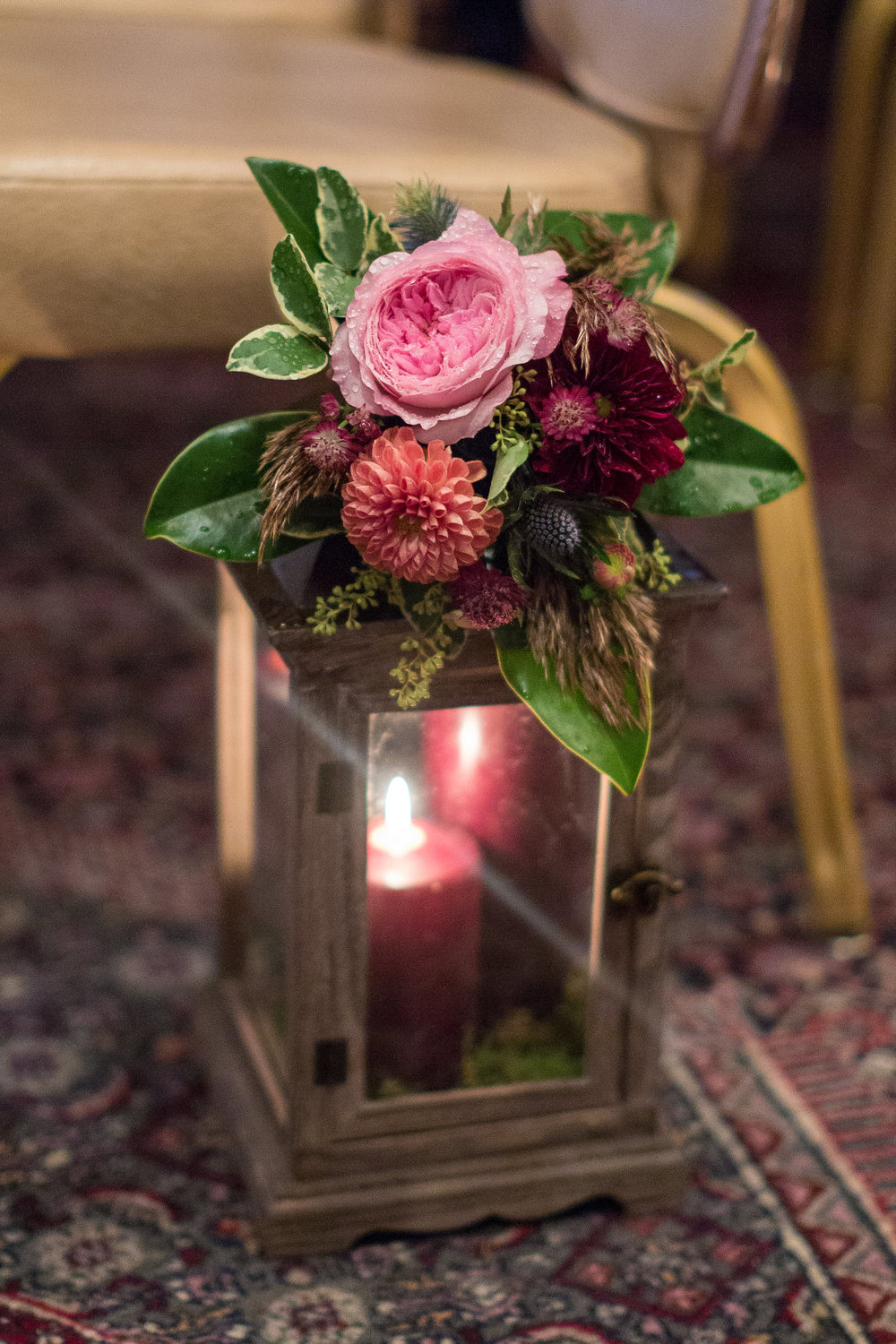 Wooden lanterns with marsala candles were made even prettier with small arrangements of garden roses, dahlias, and greenery.