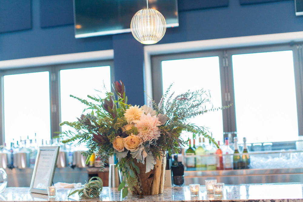 A beach wedding never feels complete without our driftwood vase making an appearance - and it always looks so different!  This wild look of dusty miller, roses, dahlias and a forest worth of greenery made this arrangement a great statement piece for the bar.