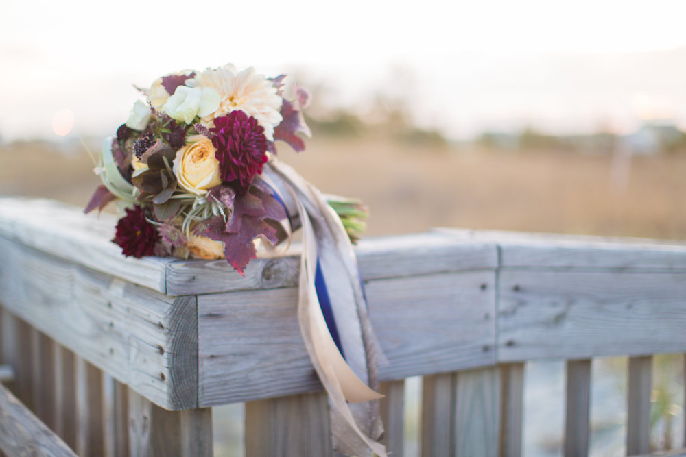 Jenna's bouquet was a staff favorite, made with airplants, burgundy and white dahlias, roses, and seasonal leaves.  We loved her trailing ribbon tails and range of color.