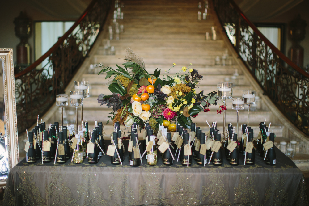 The couple's placecard table was lined with mini bottles of champagne as favors for guests.  We dressed it up with a fun linen, diana candleholders and a gorgeous arrangement of persimmon, dahlias, roses, hydranges, and foliage.