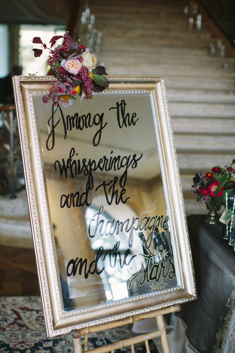 "Our  mirrored sign  read, ""Among the whisperings and the champagne and the stars,"" to inspire guests to dance the night away in romance just like in The Great Gatsby."
